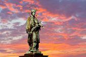 sculpture on Karluv Bridge in Prague on sunset background