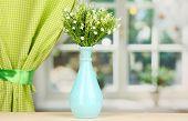 Decorative flowers in vase on windowsill