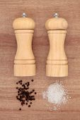 Salt and pepper grinders with loose condiments over papyrus background.