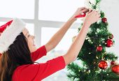 christmas, x-mas, winter, happiness and people concept - smiling woman in santa helper hat decoratin