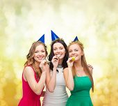 celebration, friends, bachelorette party, birthday concept - three smiling women wearing blue hats a