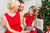 family, christmas, x-mas, winter, happiness, technology and people concept - smiling family with tab