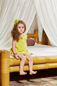 Little girl sits on edge of bed with bamboo frame