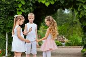 Two little girls and boy play in rock-paper-scissors standing on walkway in summer park
