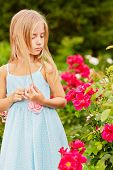Little girl dressed in polka-dot gown look at rosebush in summer park