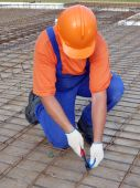 stock photo of bender  - Bar bender fixing steel reinforcement for house concrete floor slab - JPG