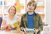 Portrait of happy young boy checking out books from library with librarian in background