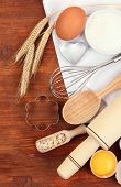 Cooking concept. Basic baking ingredients and kitchen tools on wooden table