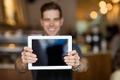 stock photo of waiter  - Male cafe owner showing digital tablet in cafeteria - JPG