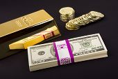 Gold coins and a gold bar with a pile of American cash for use as any investment or transactional in
