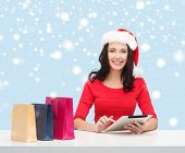 christmas, x-mas, online shopping concept - woman in santa helper hat with gift box and tablet pc co