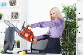 Beautiful Girl At The Office Cuts The Monitor With A Chainsaw