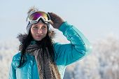 Winter young woman with ski goggles in snow mountains