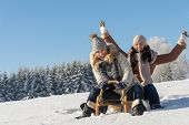 picture of toboggan  - Two girlfriends sledge downhill in sunny wintertime snow wooden sledge - JPG