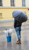 Man Selling Umbrellas Stood In Street
