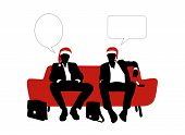 Two Businessmen Speaking Seated On A Sofa In Red Christmas Hats