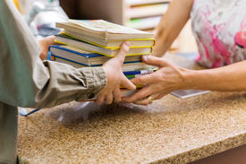 image of librarian  - Cropped image of female librarian taking books from boy at checkout counter in library - JPG