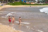 WELIGAMA, SRI LANKA - MARCH 7, 2014: Young tourists walking on sandy beach. Tourism and fishing are