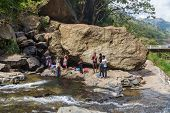 RAVANA FALLS, SRI LANKA - MARCH 2, 2014: Local men having fun at Ravana falls, popular sightseeing a