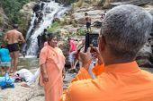 RAVANA FALLS, SRI LANKA - MARCH 2, 2014: Local tourist taking photos with mobile phone at Ravana fal