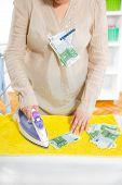 Woman ironing money, money laundering concept