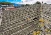 stock photo of asbestos  - Roof covered with asbestos cement sheets in a very bad state of repair - JPG