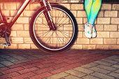 Women feet in sneakers alongside a bicycle