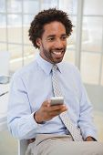 Smiling young businessman with mobile phone looking away at a bright office