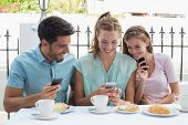 Portrait of three happy friends reading text message in the caf�?�©