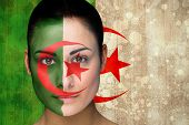 Composite image of beautiful football fan in face paint against algeria flag in grunge effect