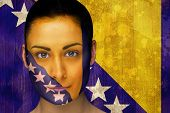 Composite image of beautiful football fan in face paint against bosnia flag in grunge effect