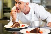 Closeup portrait of a smiling male pastry chef eating strawberry by dessert in the kitchen