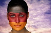 Composite image of beautiful brunette in german facepaint against scenic landscape with blue cloudy sky