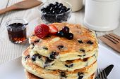 Blueberry Pancake Closeup with syrup pitcher, wooden spatula and fork, blueberry bowl and other items set out for a homemade breakfast. Horizontal format.