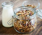 Open glass wire bail jar of granola mixture with milk on wooden background