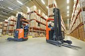 image of warehouse  - two young workers men in uniform at warehouse with forklift facilities - JPG