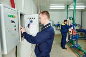 electrician in front of fuseboard equipment together with heating engineer in bioler room
