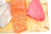raw set of sea fish food : salmon , red tuna, and sole fish chunks served on wooden plate isolated o