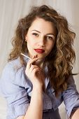Stylish emotional girl with red lips and curly hair is smoking.