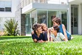 foto of lie  - happy family lying  on grass in front of house - JPG
