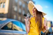 stock photo of panama hat  - Young traveling woman with photo camera and panama dressed in yellow dress walking on city background - JPG