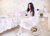 Beautiful Young Bride In A White Dress With A Wedding Bouquet Of Pink Roses Sitting In Her Bedroom I