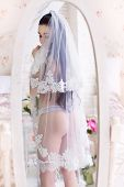 image of garter  - Beautiful young bride in the veil and with garter stands in front of the mirror - JPG