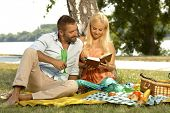 Happy casual couple reading book at picnic, outdoor. Attractive caucasian blonde woman, handsome man