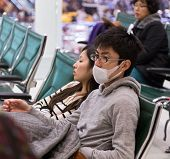 DOHA, QATAR - FEBRUARY 18, 2014: Young Asian man wearing protective mask in the waiting area of Doha