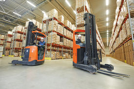 stock photo of forklift  - two young workers men in uniform at warehouse with forklift facilities - JPG