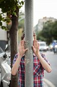 Boy With Hands Up Behind A Lamppost