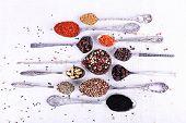 Seasonings in metal spoons on light fabric background