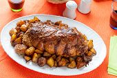stock photo of frizzle  - a tasty roast with baked potatoes on a table with a tablecloth orange - JPG