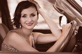 Smiling beautiful brunette woman driving a car. Image with Instagram-like filter